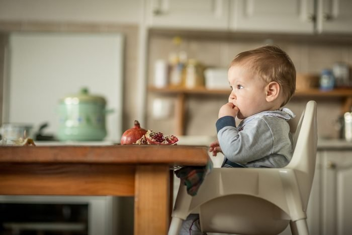 Portrait Of Happy Young Baby Boy In High Chair