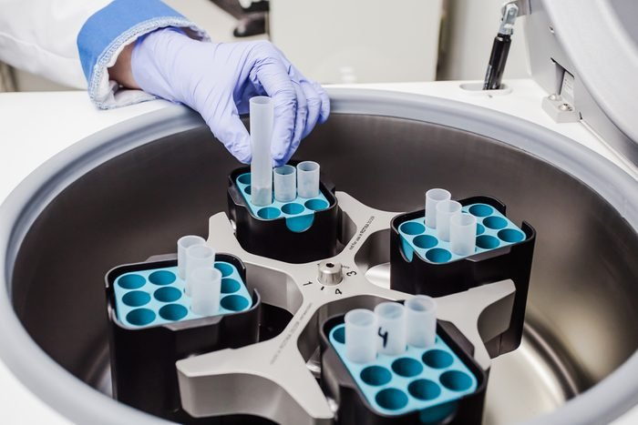 Grey centrifuge to obtain the results of a blood test, with uniformly arranged tubes. Medical worker in blue gloves inserts or take the tube from the centrifuge.