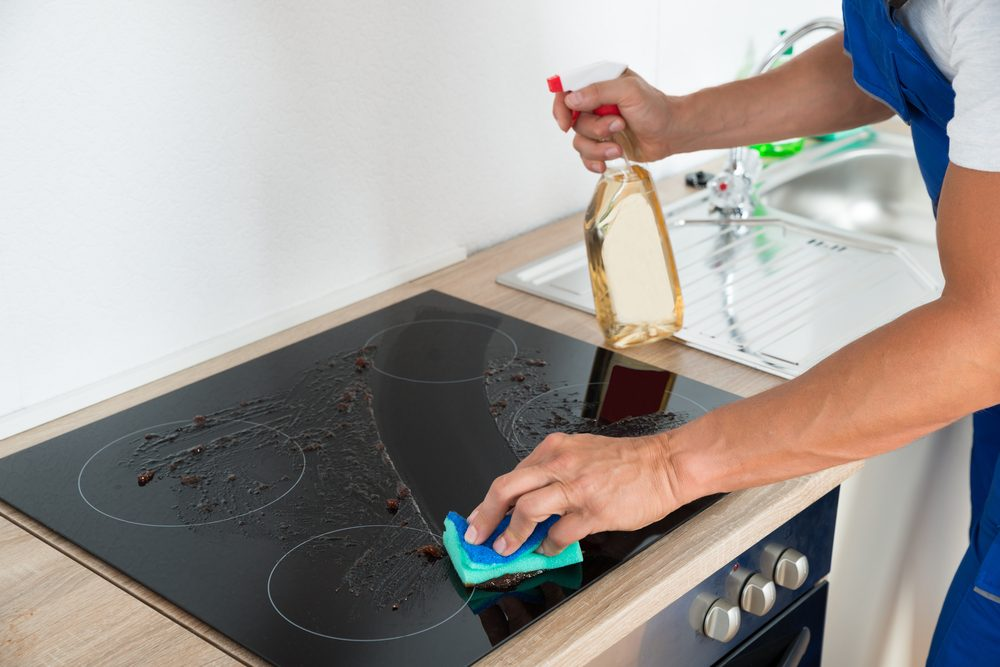 Cropped image of male janitor cleaning induction stove in kitchen