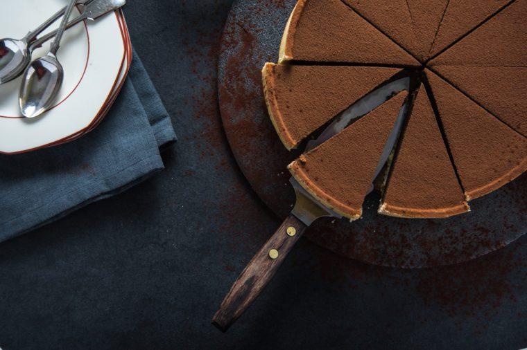 Sliced chocolate tort on dark background, overhead view