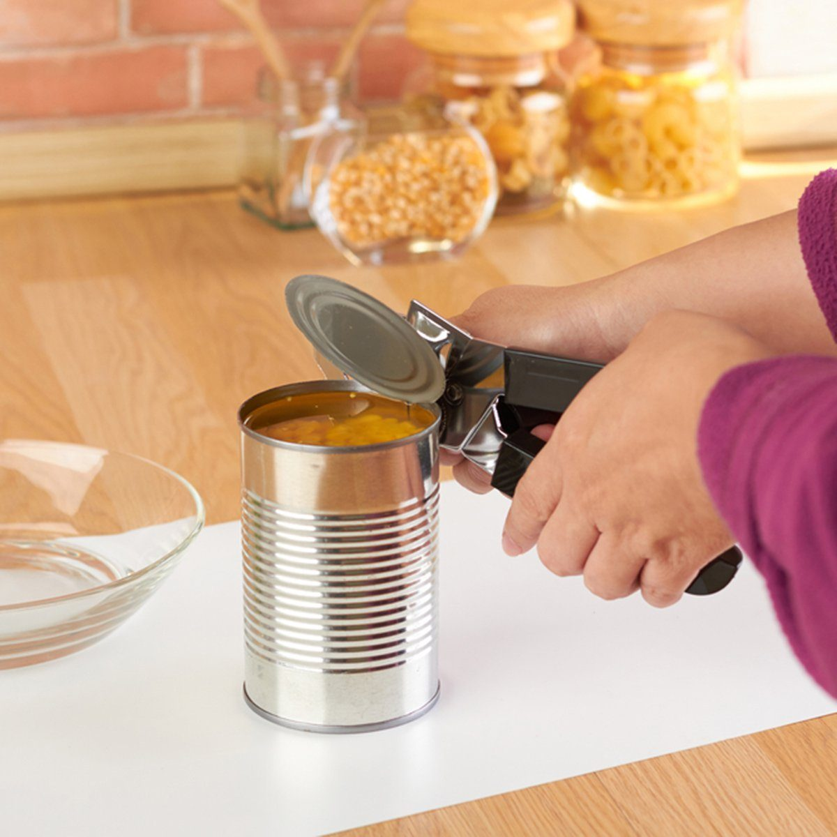 Woman opening a can of corn with can opener in the kitchen