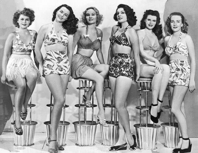 VARIOUS United States: c. 1952. Six attractive young women in two piece bathing suits sit in a row on modern stools.
