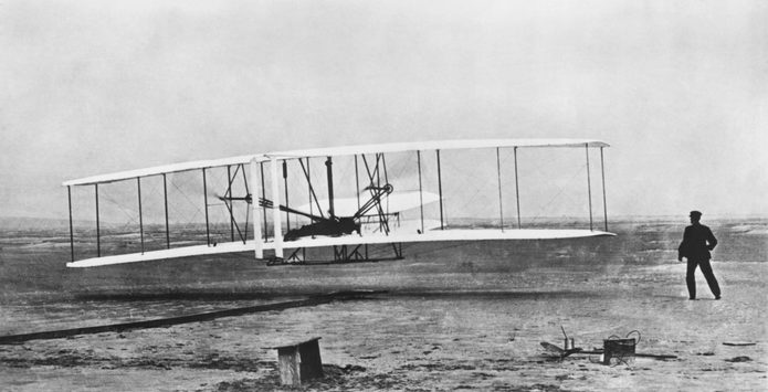 VARIOUS Kitty Hawk, North Carolina: December 17, 1903 Orville Wright flying during the first powered and sustained flight while Wilbur is on the ground at right.