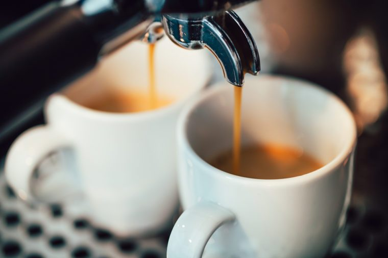 Close up image of espresso pouring into white cups