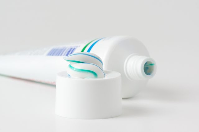 toothpaste tube with a small amount of toothpaste on the cap