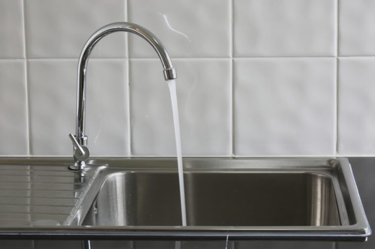 Metal faucet in a kitchen is open water