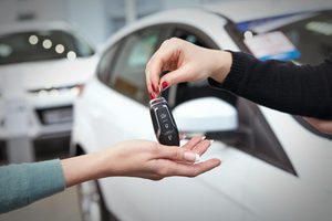 Here you go. Horizontal cropped hot of a car dealer passing keys to a new car female owner