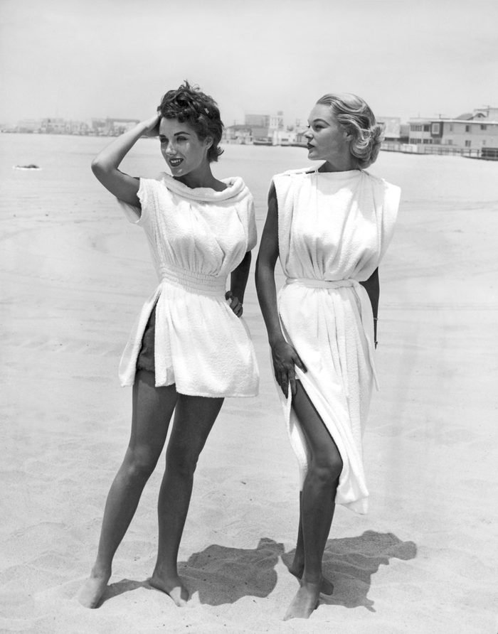 VARIOUS England: 1954 Terry-cloth coverups look delightful on these two models standing on a beach.