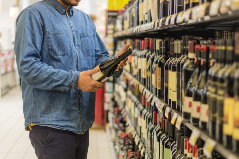 Man is buying a bottle of wine at the supermarket.