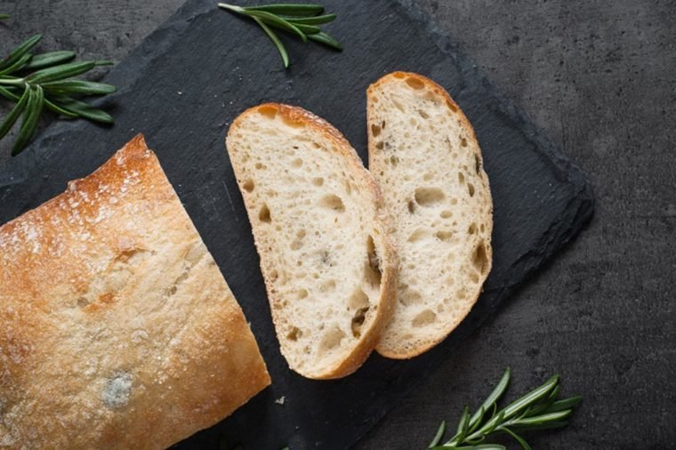 Italian ciabatta bread on black slate board with herbs and olives, Top view