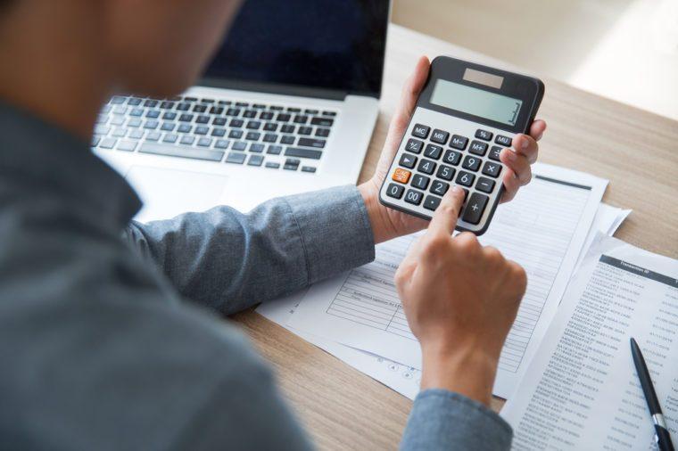 Unrecognizable businessman using calculator