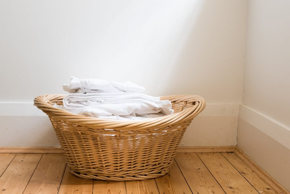 Wicker laundry basket with folded white washing on wooden floorboards with window light