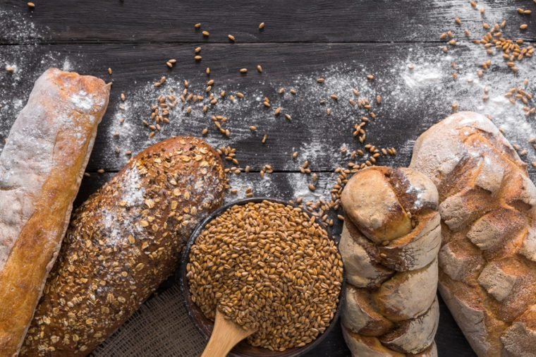 Bread border on dark wood with copy space background. Brown and white whole grain loaves still life composition with wheat flour sprinkled around. Bakery, cooking and grocery store concept.