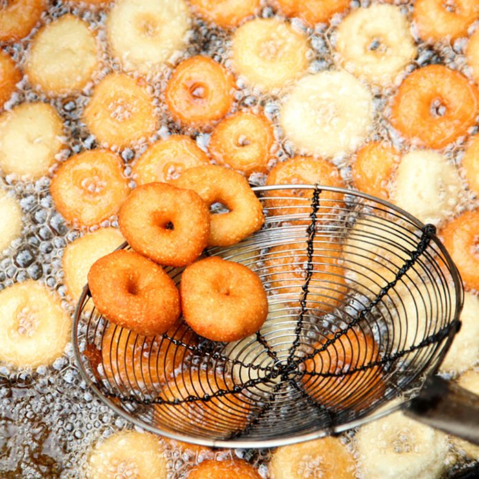 Deep frying medu vada in the pan. Medu Vada is a savoury snack from South India, very common street food in the India
