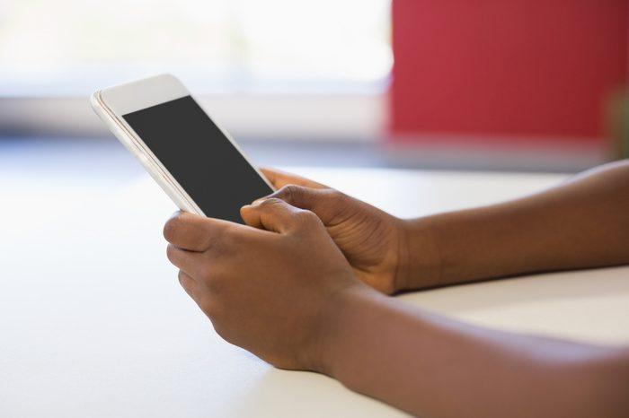 Schoolgirl using mobile phone in classroom at school