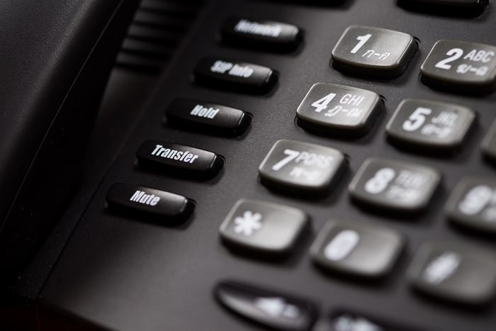 A close up of a Black office IP Phone on a desk