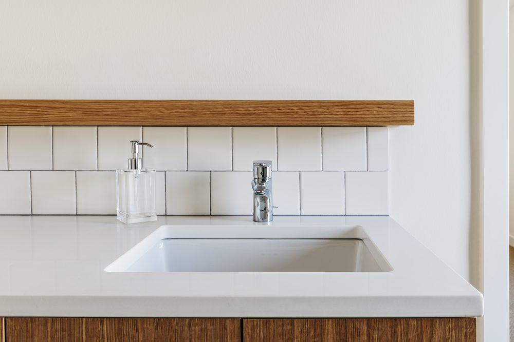 Modern bathroom sink with subway tile backsplash with wood details.