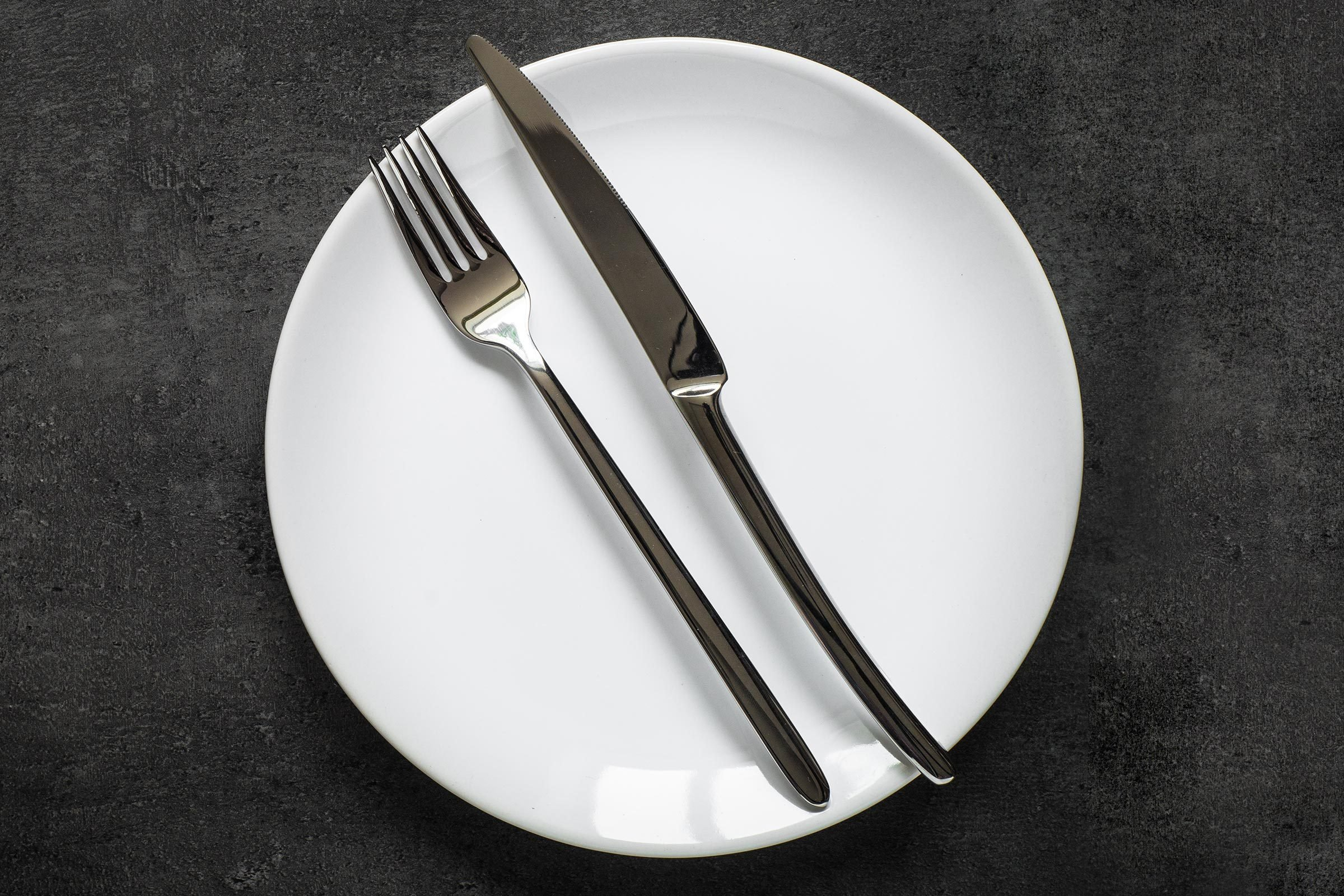Table setting. Fork knife and white plate at dark slate table. Dark food background. Top view copy space.