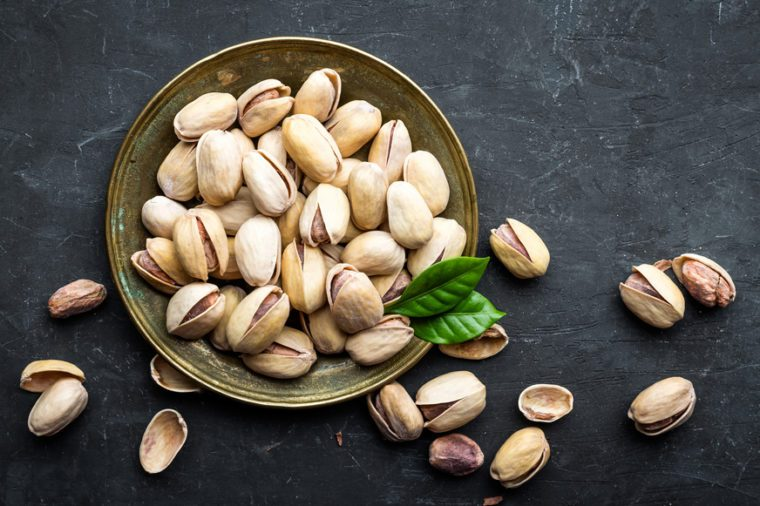 Pistachios nuts on dark background, top view, healthy snack