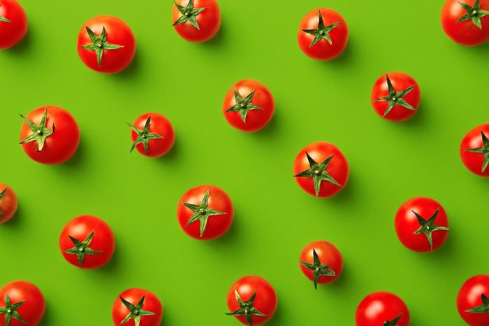 Cherry tomato pattern on a green background. Flat lay, top view