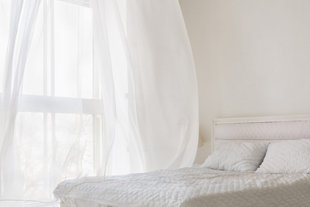 Abstract white flying curtain in white room with bed