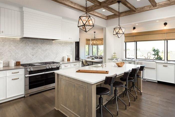 Kitchen Interior with Island, Sink, Cabinets, and Hardwood Floors in New Luxury Home. Features Elegant Pendant Light Fixtures, and Farmhouse Sink next to Window