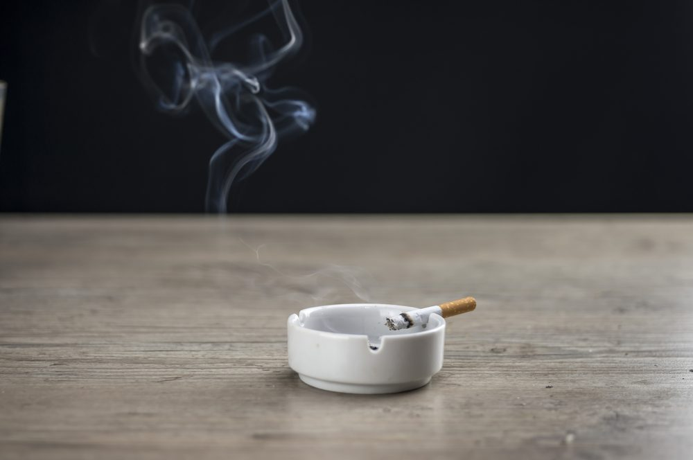Lit cigarette burning in ashtray close up