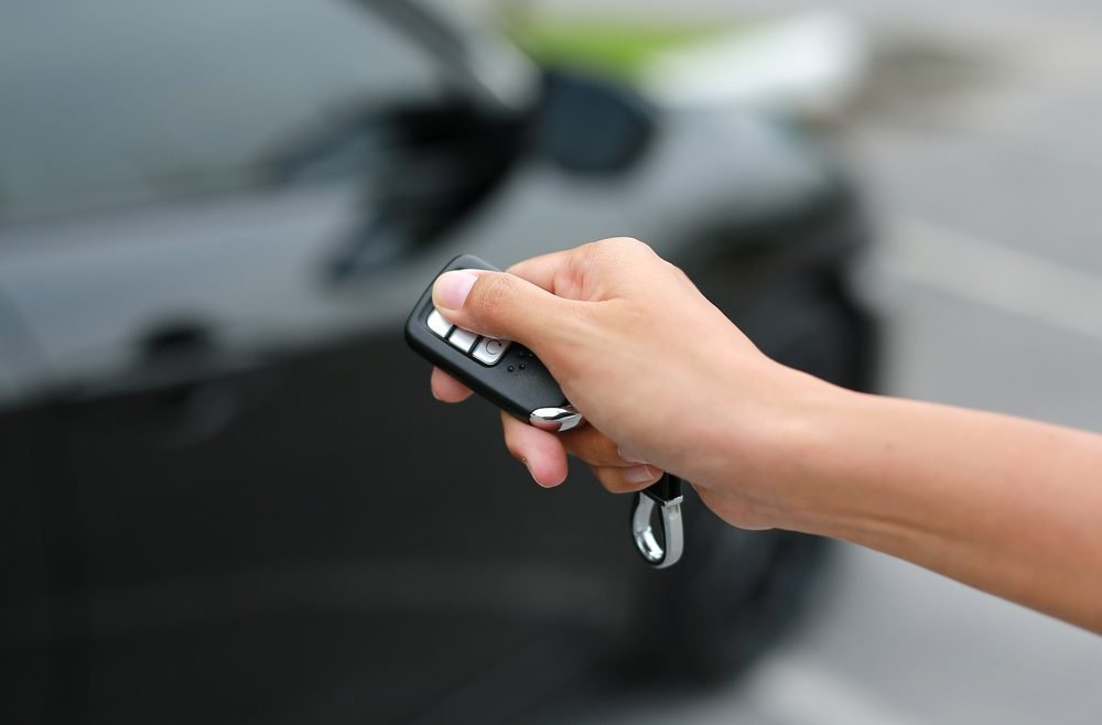 Women hand pressing the button on the remote to lock or unlock the car