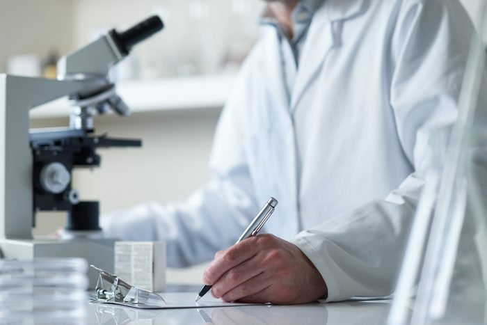 scientist conducting research with microscope selective focus