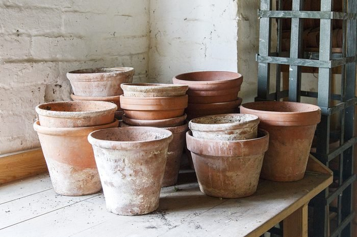 Terracotta clay plant pots stacked in a garden shed