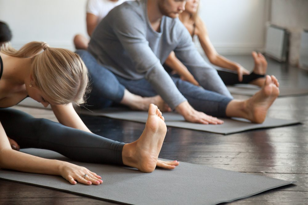 Young sporty people practicing yoga lesson with instructor, sitting in Janu Sirsasana exercise, Head to Knee Forward Bend pose, working out, indoor close up image, studio. Wellbeing, wellness concept