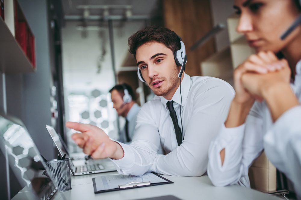 How can I help you? Beautiful call center workers in headphones are working at modern office.