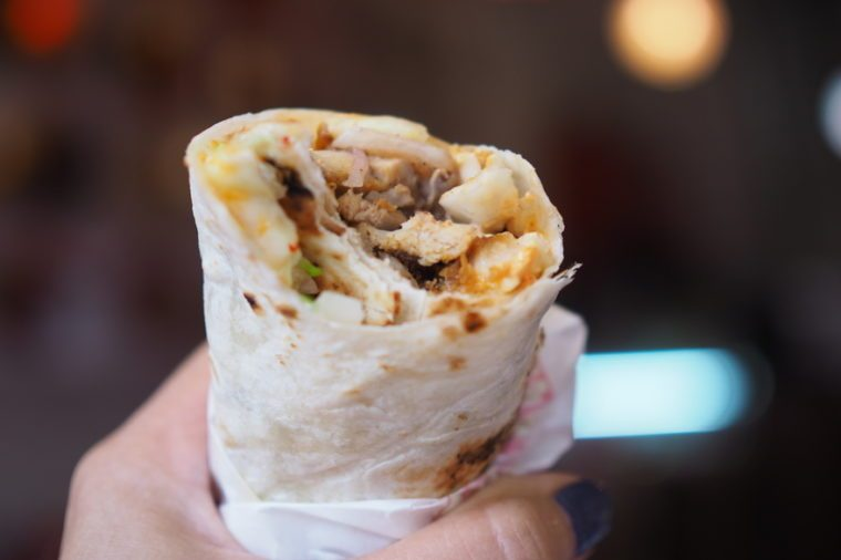 Hand holding chicken kebab