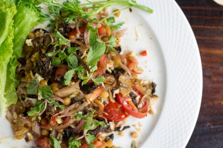 Burmese Tea Leaf Salad with vegetables and on white dish