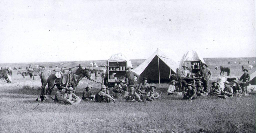 Art Cowboys around chuck wagons, 1887 in the Dakota Territory