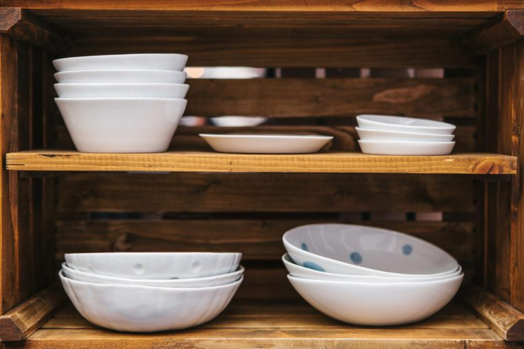 Many ordinary ceramic plates on wooden shelves. Kitchen accessories for cooking.