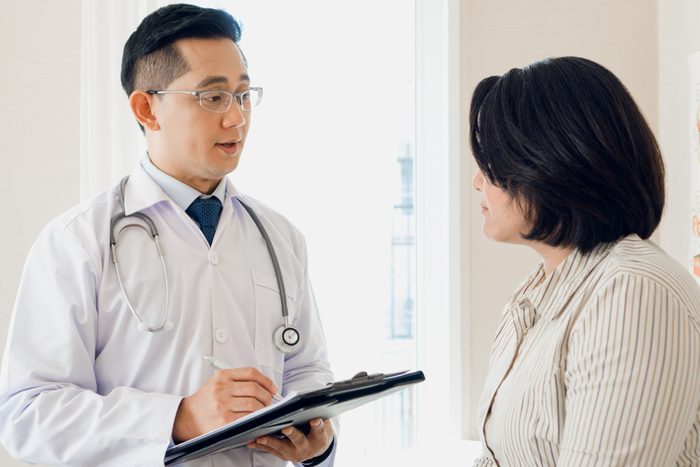 Asian doctor talking with middle aged woman in clinic asking symptoms for examination.