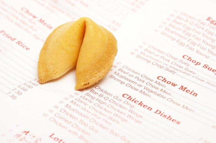 A Chinese food take out menu with a fortune cooke.