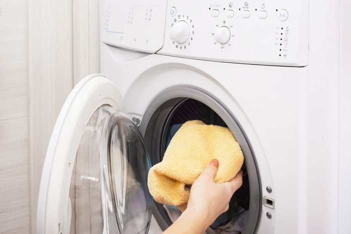 Woman loading laundry to the washing machine, Preparing the wash cycle, close up of a washing machine loaded with clothes, hand taking color towels