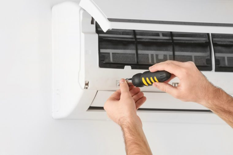 Male technician fixing air conditioner indoors