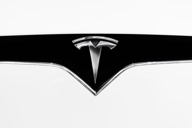 VARIOUS Tesla Motors electric car emblem on a hood of white 2017 Tesla X, logo trademark, closeup