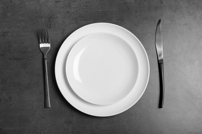 Empty dishware and cutlery on gray background, top view. Table setting