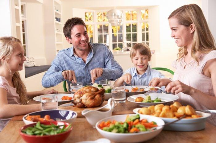 Happy family having roast chicken dinner at table