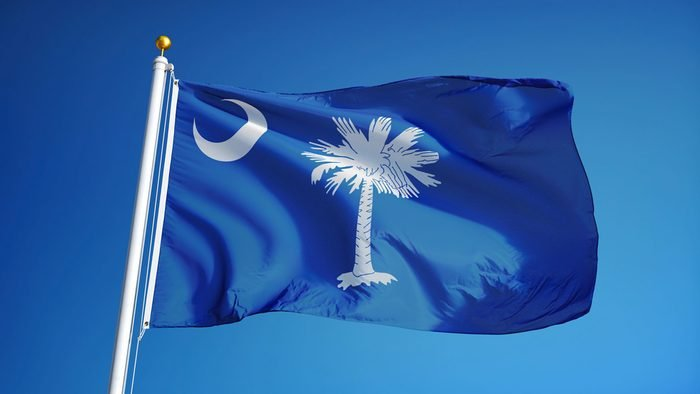 South Carolina (U.S. state) flag waving against clear blue sky, close up, isolated with clipping path mask alpha channel transparency, perfect for film, news, composition