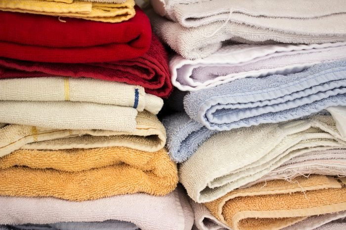 Stacked colorful household towels. There are red, blue and yellow, and they're stacked in a closet.