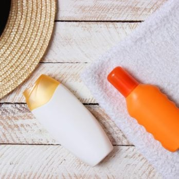 sunscreen, towel, hat, glasses on a wooden background. minimalism, the top view, flatlay