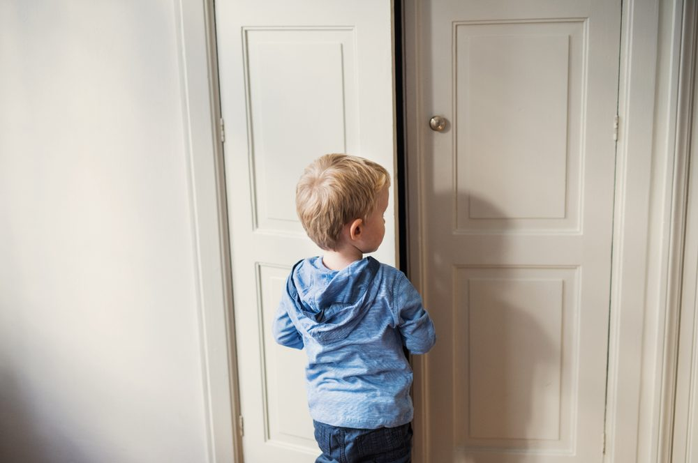 A rear view of toddler boy standing near door inside in a bedroom.