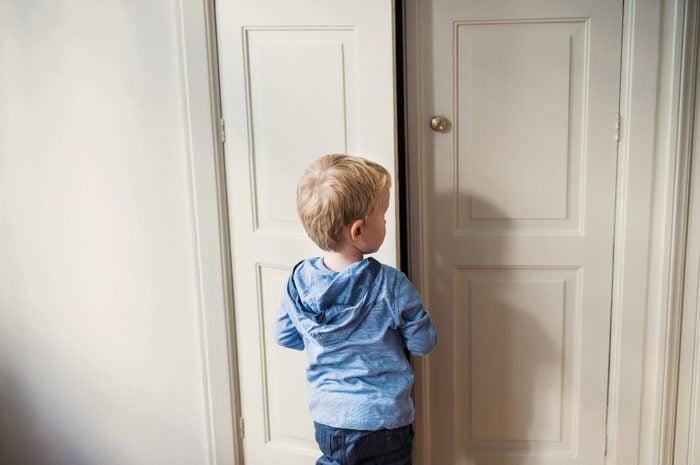 A rear view of toddler boy standing near door inside in a bedroom.