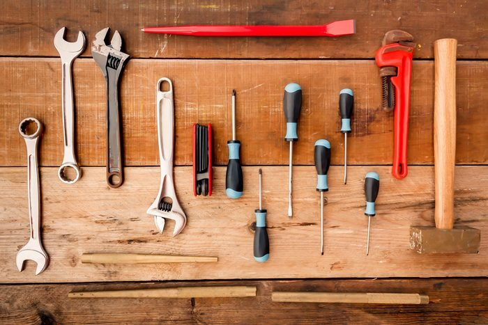 Hand tool complete set the Wrench, screwdriver, Phillips screwdriver, flat crowbar,brass hammer,pipe wrench,punch,Hex wrench on wood background.