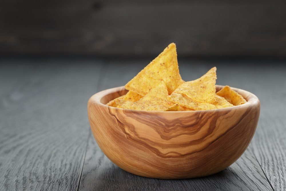 tortilla chips in olive wood bowl on wooden table, selective focus